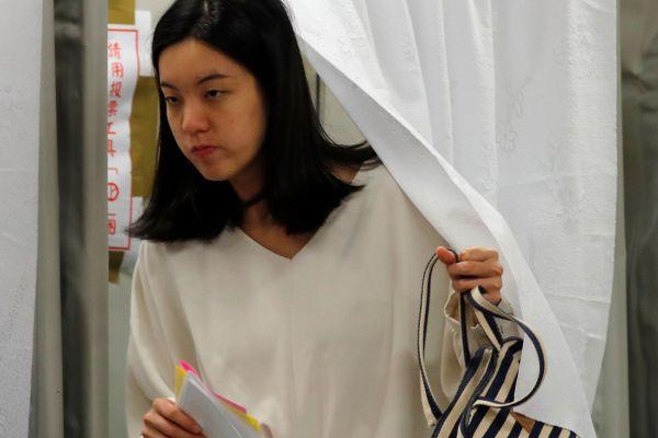 総統選が行われている台北の投票所を出る女性=2020年1月11日、ロイター