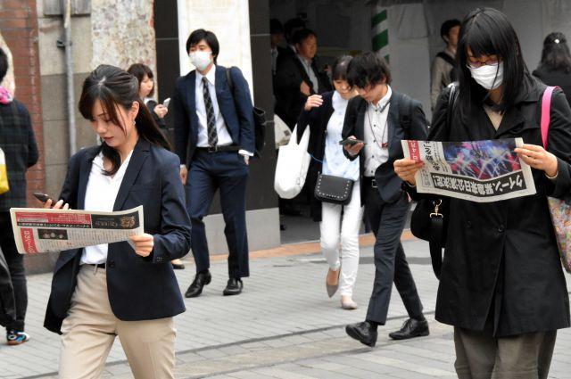 「クイーン来日決定」の号外を眺める人々=2019年4月17日、東京都港区の新橋駅前