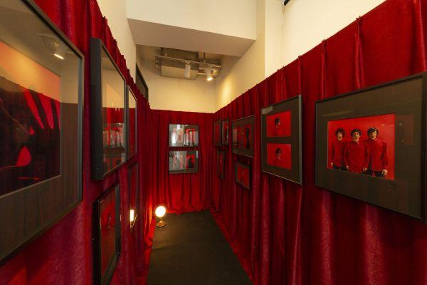 顔のほおやあごの骨が未発達な「トリーチャーコリンズ症候群」の当事者3人の作品を並べた赤い部屋