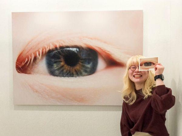 「見た目問題」がテーマの写真展「無自覚なボクが、いま言いたいこと。」に参加する、アルビノの神原由佳さん。自身の瞳を写した作品の前でポーズ