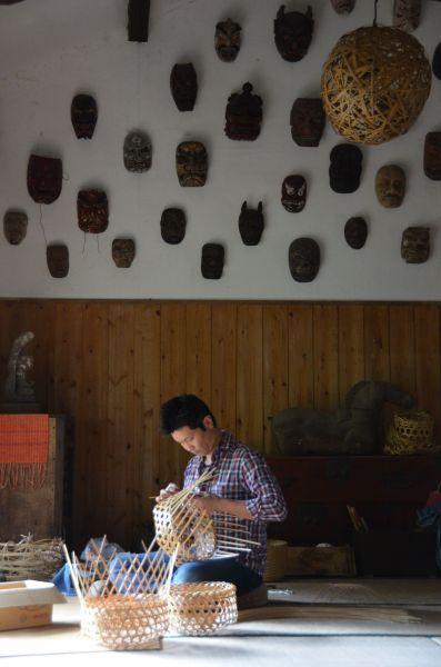かごを編む林田さん。高見さんらも驚くほどあっという間に覚えイベントなどで売っている。壁には高見さんが集めた神楽の面が並ぶ。