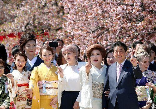 安倍晋三首相(右から2人目)と記念写真を撮る「桜を見る会」の参加者たち=2019年4月13日午前9時57分、東京都新宿区