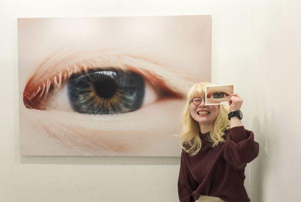 特徴的な外見で苦労する「見た目問題」がテーマの写真展で、自らの目を写した作品前でポーズを取る神原さん