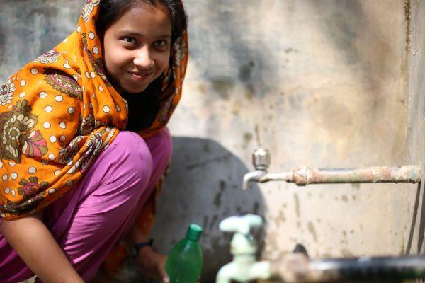 AANの援助でつくられた地下水の浄化施設から水をくむ少女=2013年、バングラデシュ