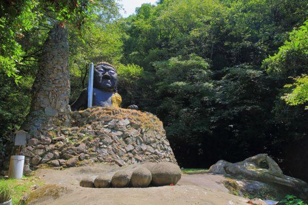 山あいに建つ源宗坊寺内に造られた「不動明王大仏」(広島県呉市・6メートル)。寺を創建した僧侶・稲田源宗が一人で手がけた。元々は、更に大きな仏像の「胎内仏」となる予定だったという