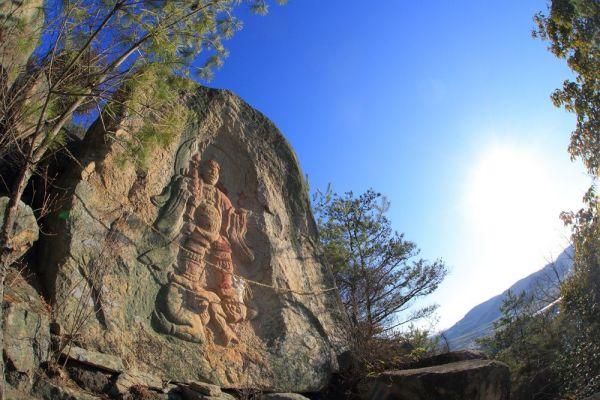岡山県倉敷市内の山頂に彫られた「毘沙門天立像」(4メートル)。夕日の光に、朱色の山肌が映える