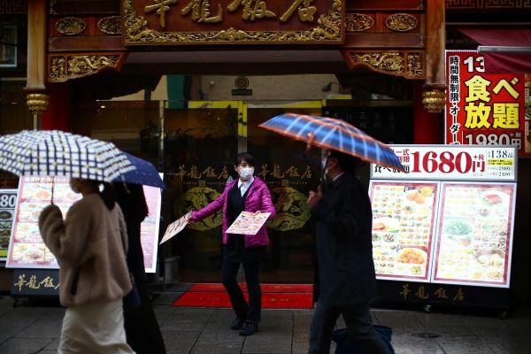 横浜中華街、マスク姿で客にメニューを見せるレストランの従業員=2020年3月10日、横浜、神奈川県