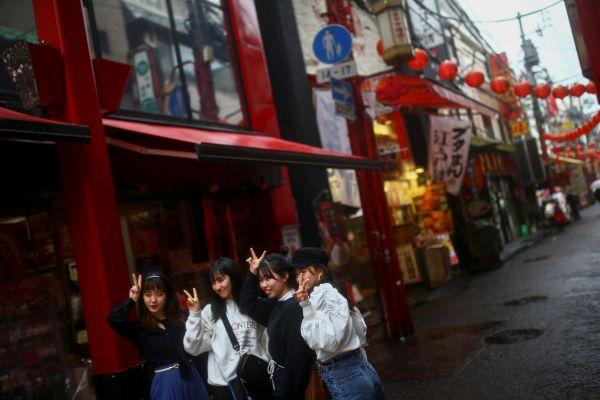 自撮りする観光客、人影が少ない横浜中華街=2020年3月10日、横浜、神奈川県