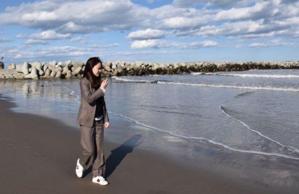 福島県富岡町の海岸をスマホで撮りながら、生放送を配信する甜甜さん=2020年3月11日、本人提供
