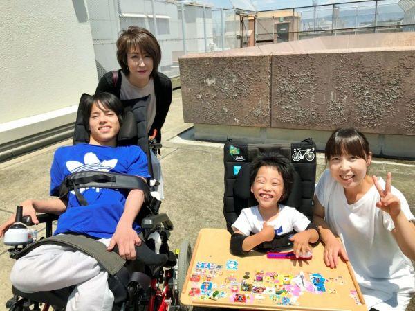渋谷友哉さんと母の貴代さん(左)。病院で友哉さんのことを「お兄ちゃん」と言って慕っているという同じ病の子どもと、親との記念写真=貴代さん提供