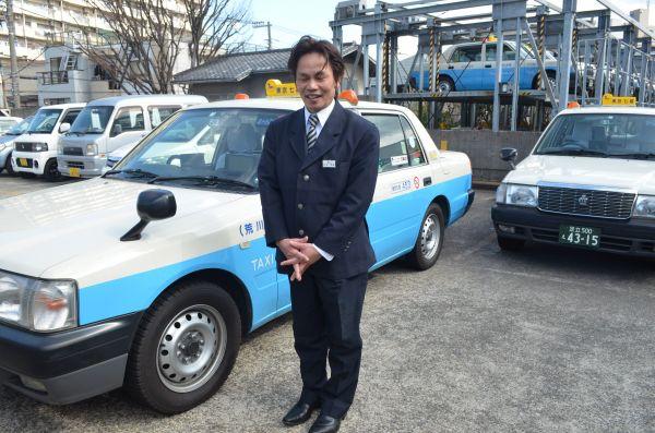 東京七福交通のタクシーの前に立つ伊東さん