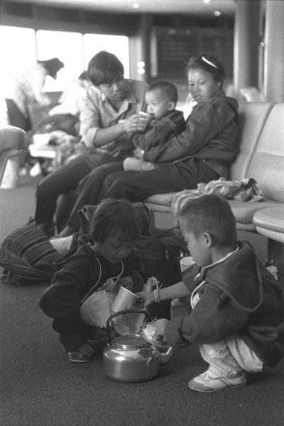 米国行きの途中で成田に立ち寄ったインドシナ難民。大切に持ち歩くやかんから水をくむ子どもの姿も 1988年3月24日 千葉県成田市、成田空港