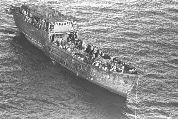 沖縄県・那覇沖の西3キロの東シナ海で発見され、巡視船にえい航されるベトナムの難民船=1989年8月23日、朝日新聞社写真部、永曽康仁撮影