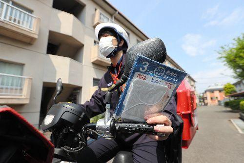 政府が配布する布マスクをバイクで配達する郵便局員=2020年4月17日、東京都世田谷区、遠藤啓生撮影