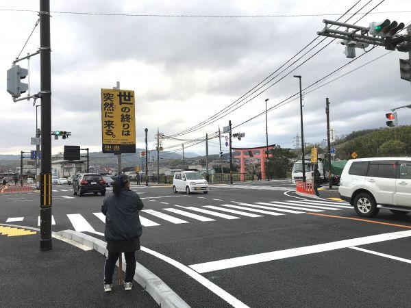 プラカードによる街宣部隊も密集を避け、それぞれ横断歩道を挟んで反対車線側に立つ