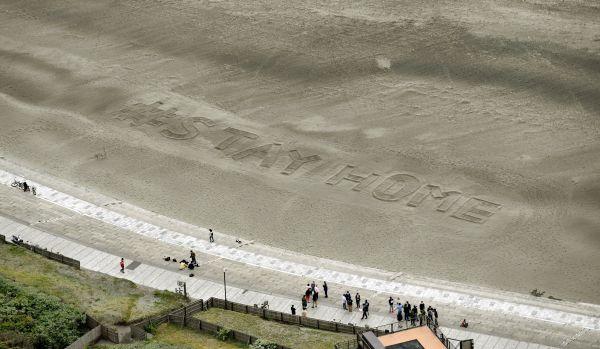 地元住民らが海岸にトンボで書いた「STAY HOME」の文字=2020年4月27日午後0時44分、神奈川県藤沢市、朝日新聞社ヘリから、福留庸友撮影