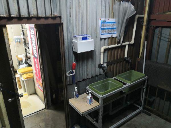 前進社の出入り口、傘立てがあったスペースにDIYで設置された手洗い場=前進社提供