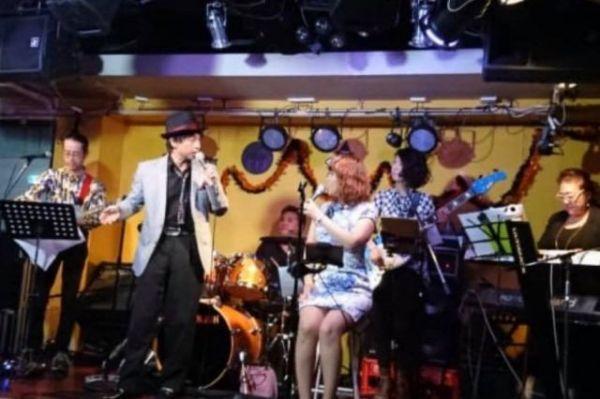 ライブハウスでバンドと共に歌うKeikoさん。多発性硬化症を患ってからは、座ってステージに