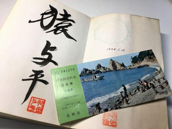 サルとの日々を記録した肥田さんの著書『波勝崎に野猿と生きる』に残る直筆のサイン。「猿与平」の文字のほか、フルネームを彫り込んだはんこも見える。右手にあるのは、波勝崎苑時代の入場チケットの半券。