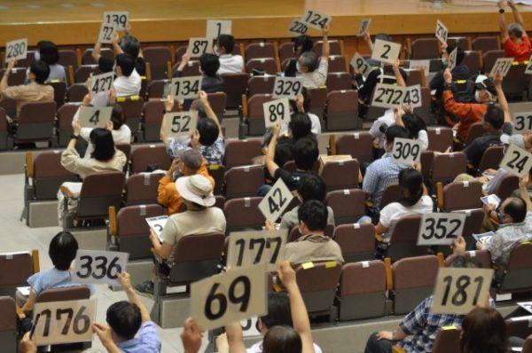 競りの練習で自分の番号が記されたシートを掲げる参加者たち