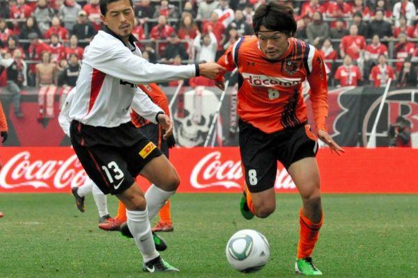 激しく競り合う大宮の東慶悟選手(右)と浦和の鈴木啓太選手=2011年2月20日、さいたま市大宮区のNACK5スタジアム