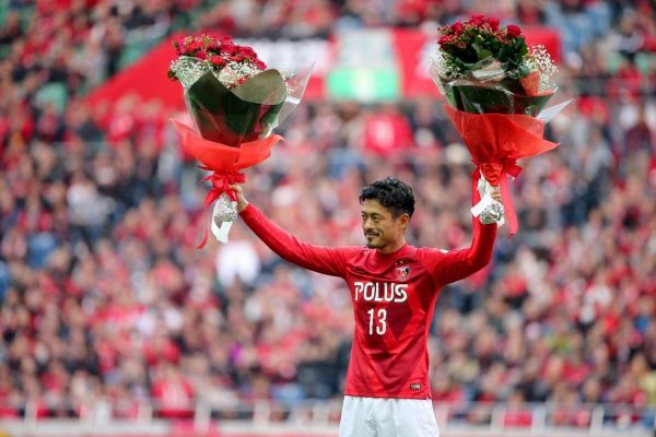 引退を表明し、試合後のセレモニーで花束を掲げる鈴木啓太さん=2015年11月22日、長島一浩撮影