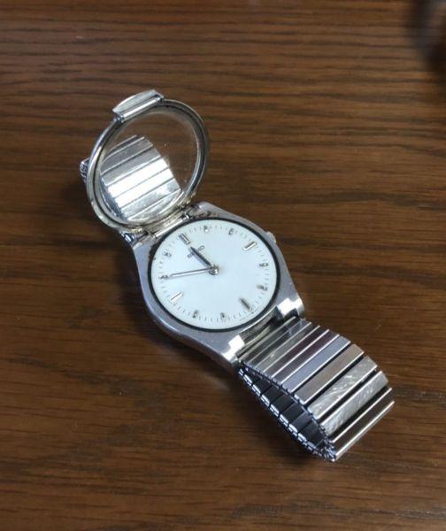 アニメ「名探偵コナン」に出てくる時計型麻酔銃のように、ガラスのふたを開くことができる時計。時計の針を指で直接触って、時間を確認できる