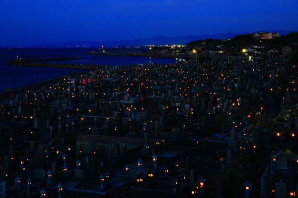 夕闇が迫る頃、墓を囲む用に立つ石灯籠に一つ、二つと明かりがともされていく。視界がぼんやりとにじみ、見る人を幽玄の世界へと誘うようだ。毎年お盆の夕暮れから夜にかけてだけ楽しめる、特別な景色。