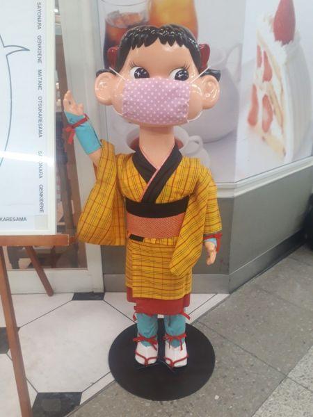 「不二家」三島ステーション店のペコちゃん。独自の衣装をまとい、コロナ禍ではマスクも着用している。