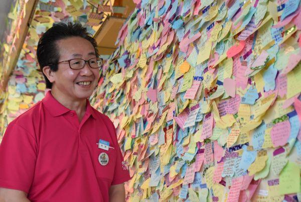 来園者から寄せられた「としまえんへのメッセージ」を紹介する事業運営部長の内田弘さん。付箋が足りなくなり、急きょ事務所にあったものも使ったという=2020年8月、東京都練馬区