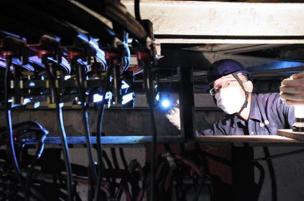 月に一度の整備で、カルーセル・エルドラドの内部にあるモーター部分を点検する佐藤さん=2020年8月、東京都練馬区