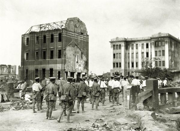 関東大震災復旧工事のため、ツルハシやスコップをかついで西掘留川にかかる荒布橋(荒和布橋)を渡る陸軍工兵隊の兵士たち。橋の親柱には「此先親父橋通行不能」の表示がある=1923年9月
