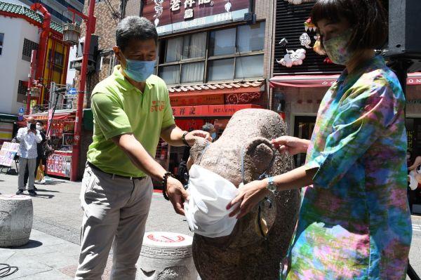 広場にある石像のマスクを外す南京町の人々=5月28日、遠藤美波撮影