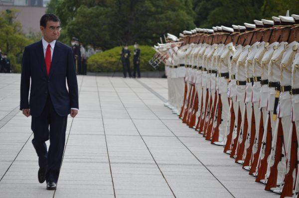 儀仗広場で栄誉礼に臨み、巡閲する河野・前防衛相。儀仗隊は白の特別儀仗服