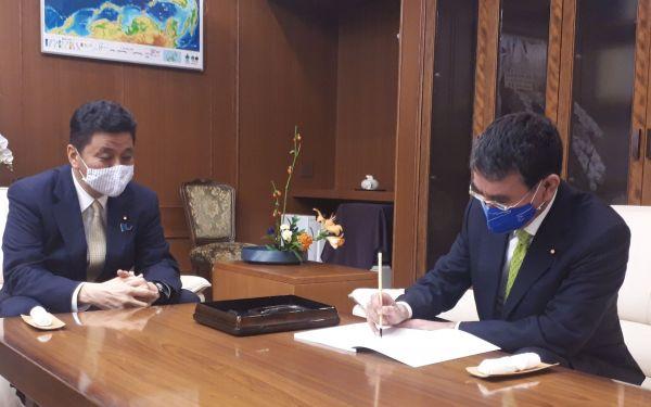 防衛大臣室で引き継ぎ書に署名する河野・前防衛相(右)と、岸信夫防衛相