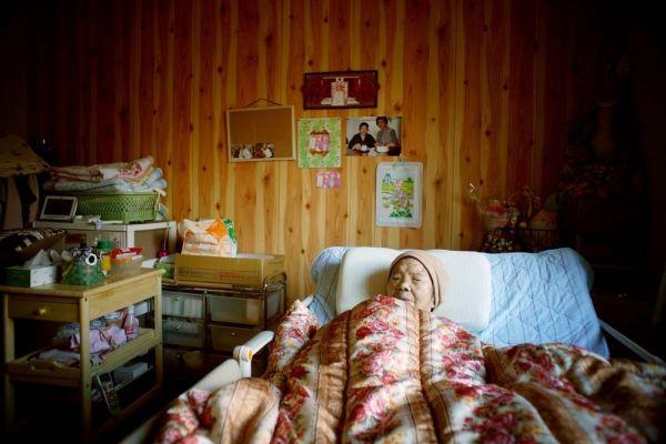 避難生活を送る三浦ミンさん。寝室には思い出の写真が飾られている=2019年12月23日午後、福島市、小玉重隆撮影