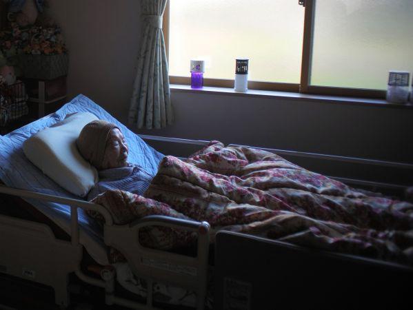 避難先の介護用ベッドで眠る三浦ミンさん=2019年12月23日午後、福島市、小玉重隆撮影
