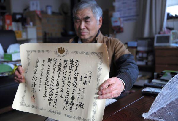 100歳の長寿を記念して内閣総理大臣から贈られた賞状を見せるミンさんの家族=2018年1月、福島市、三浦英之撮影