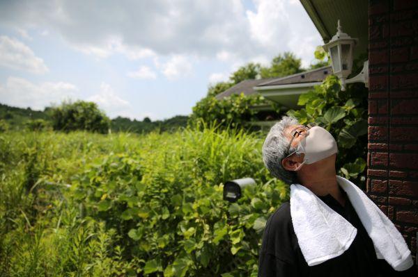夏草に覆われた自宅と屋根を見上げる今野さん=2020年8月、福島県浪江町津島地区、三浦英之撮影