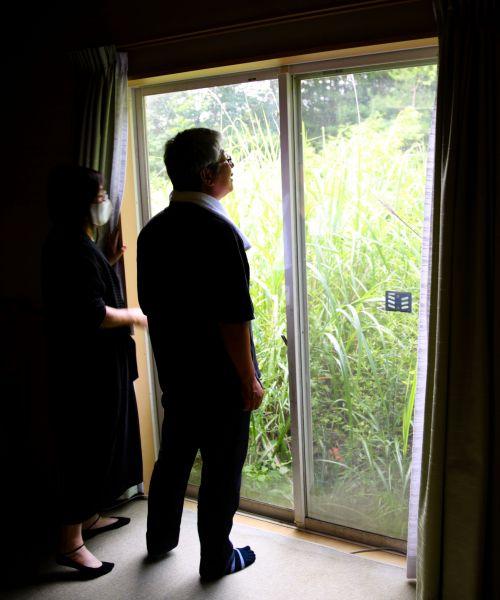 自宅の中から、かつて「庭だった場所」を見つめる夫婦=2020年8月、福島県浪江町、三浦英之撮影