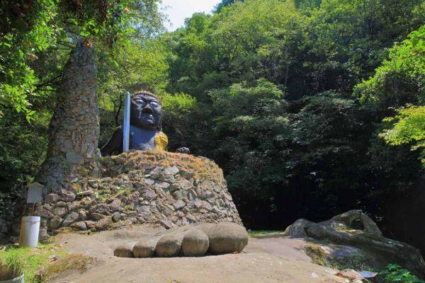 6メートルほどの不動明王像の下半身は、石垣に埋まっている。前方には、像を覆うように造られるはずだった、釈迦牟尼仏の足も