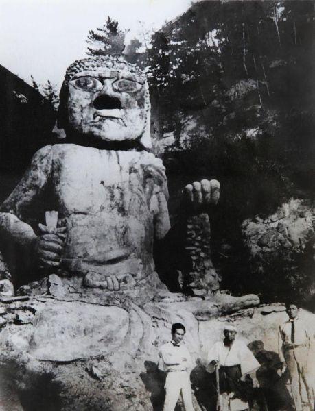 不動明王像の前で、新聞社の記者に挟まれる、源宗坊寺と仏像を建てた稲田源宗さん(右下中央)