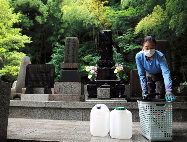 お墓の掃除をする佐々木やす子さん=2020年7月、福島県浪江町、三浦英之撮影