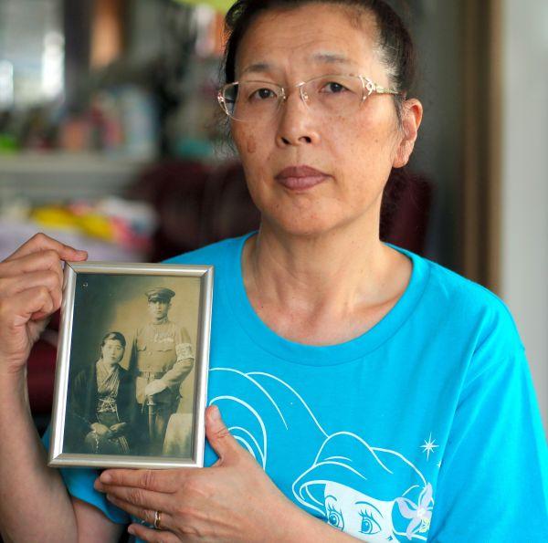 両親の写真を手に持つ三瓶春江さん=2019年9月、福島市、三浦英之撮影
