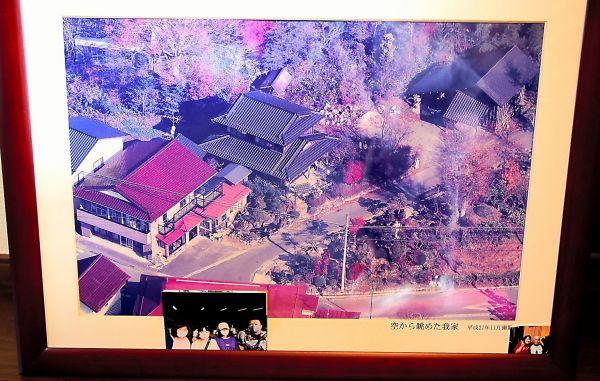 今野さんの避難先に飾られている、かつての自宅周辺の空撮写真=2020年10月、福島県須賀川市、三浦英之撮影