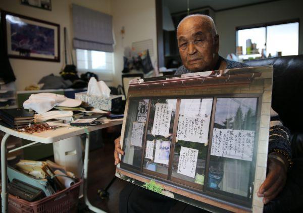 筆書きの文面を掲示していた自宅の窓の写真を掲げる今野洋一さん=2020年10月、福島県須賀川市、三浦英之撮影