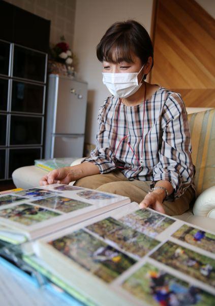 津島で暮らしていた頃の家族アルバムを見つめる門馬和枝さん=2020年10月、福島県相馬市、三浦英之撮影