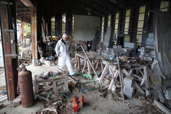 地震を受けて激しく散らばったままの石材工場のなかを歩く末永一郎さん=2018年9月、福島県浪江町、三浦英之撮影