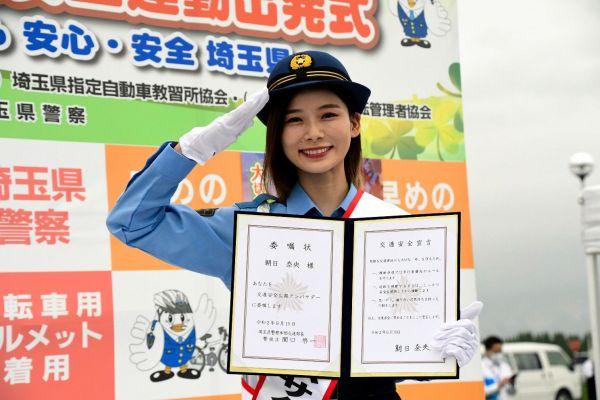 委嘱状を手に敬礼する朝日奈央さん=2020年9月19日、埼玉県警機動センター