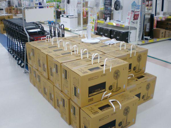 家電量販点に並んだ扇風機入りの箱。側面に、白色のタックハンドルが設置されている。